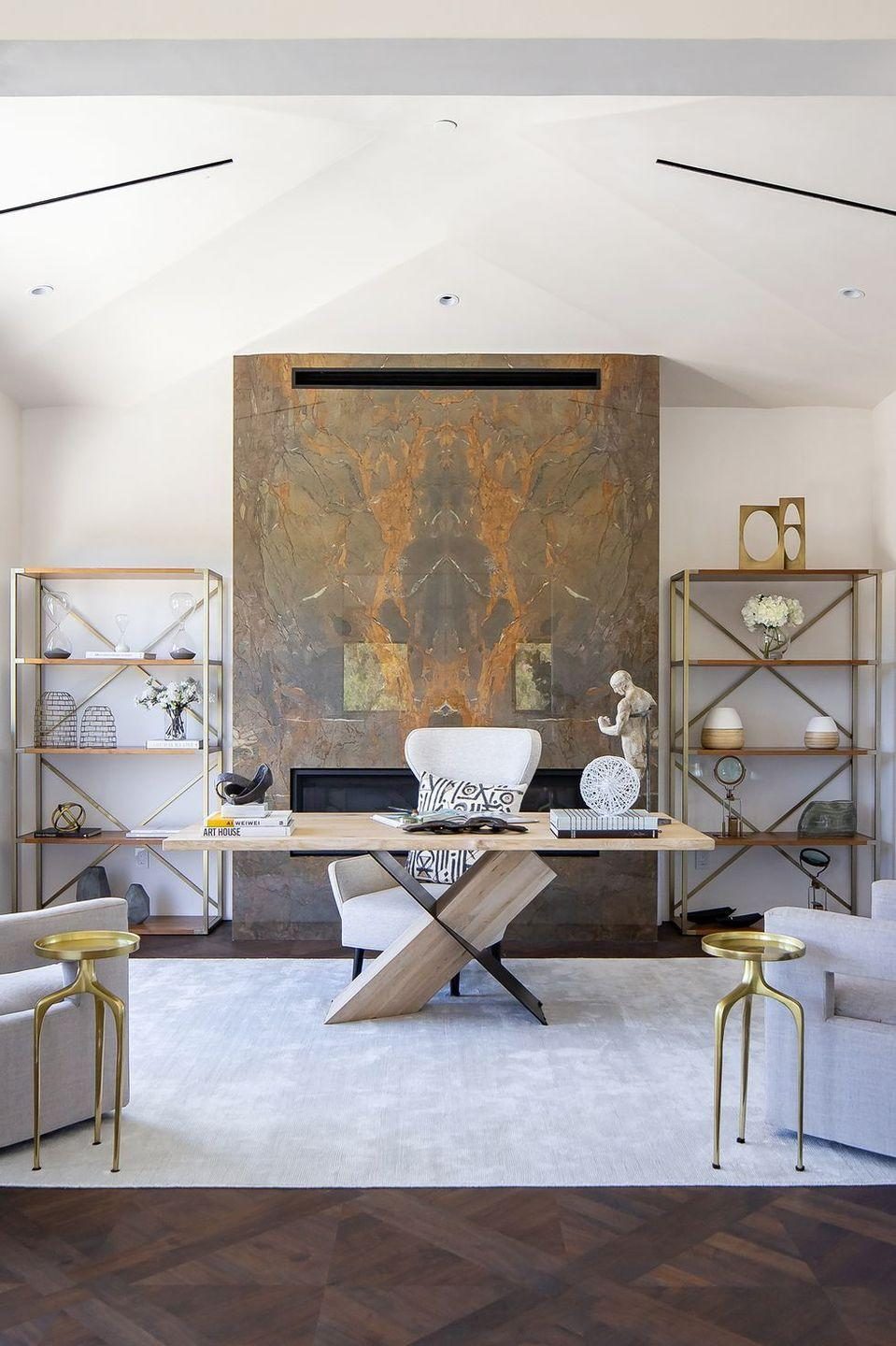 """<p>Warm and open up an airy home office with a fireplace that features an earth-toned facade, like this one in a large room <a href=""""https://www.housebeautiful.com/design-inspiration/house-tours/a33930929/breegan-jane-unica-tour/"""" rel=""""nofollow noopener"""" target=""""_blank"""" data-ylk=""""slk:designed"""" class=""""link rapid-noclick-resp"""">designed</a> by <a href=""""https://breeganjane.com/"""" rel=""""nofollow noopener"""" target=""""_blank"""" data-ylk=""""slk:Breegan Jane."""" class=""""link rapid-noclick-resp"""">Breegan Jane.</a> The marble introduces a sophisticated, formal style to the more casual elements, and it also helps to bring the scale of the ceilings down to a more intimate, human scale.</p>"""