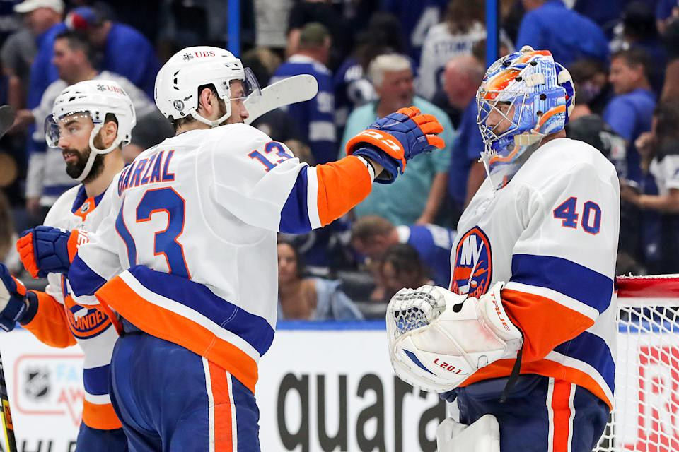 TAMPA, FLORIDA - JUNE 13:  Mathew Barzal #13 and Semyon Varlamov #40 of the New York Islanders celebrate their teams 2-1 victory against the Tampa Bay Lightning in Game One of the Stanley Cup Semifinals during the 2021 Stanley Cup Playoffs at Amalie Arena on June 13, 2021 in Tampa, Florida. (Photo by Mike Carlson/Getty Images)