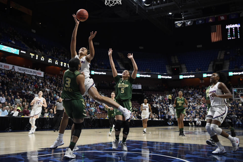 Connecticut's Olivia Nelson-Ododa shoots as South Florida's Sydni Harvey (3) and Elena Tsineke (5) defend during the first half of an NCAA college basketball game in the American Athletic Conference tournament semifinals at Mohegan Sun Arena, Sunday, March 8, 2020, in Uncasville, Conn. (AP Photo/Jessica Hill)