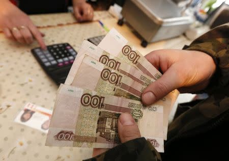 A customer holds 100-rouble banknotes while visiting a local grocery store in the village of Verkhnyaya Biryusa outside the Russian Siberian city of Krasnoyarsk