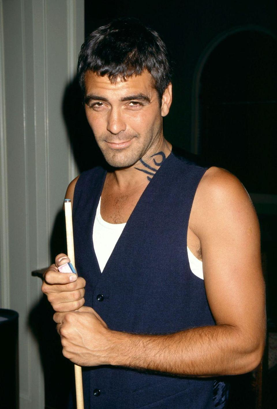 <p>Clooney poses with a pool stick during the filming of <em>From Dusk till Dawn</em> in 1995 in Los Angeles.</p>