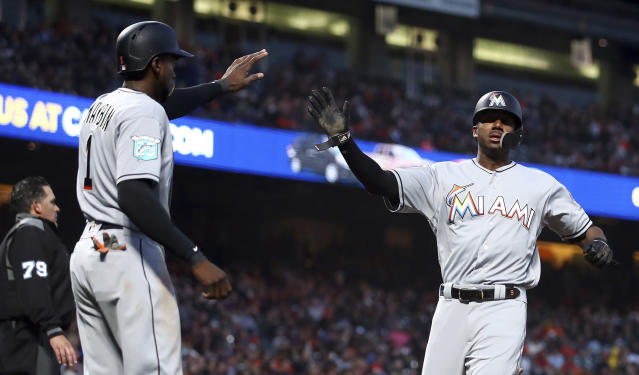 Miami Marlins' Lewis Brinson, right, and Cameron Maybin (1) celebrate after scoring against the San Francisco Giants in the inning of a baseball game Monday, June 18, 2018, in San Francisco. (AP Photo/Ben Margot)