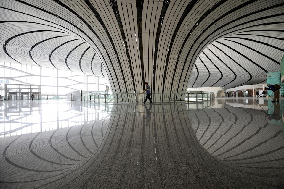 This photo taken on June 26, 2019 shows a worker walking in the terminal building of the new Beijing Daxing International Airport in Beijing. (Photo by STR / AFP) / China OUT (Photo credit should read STR/AFP via Getty Images)