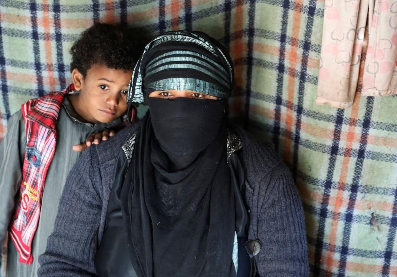 Sameera Hussein Nasser, 40, sits with one of her sons in a hut where they live at a camp for internally displaced people near Sanaa