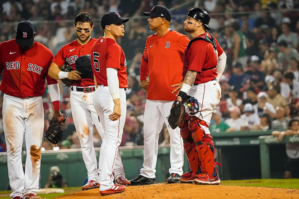 Red Sox players and manager Alex Cora look on during a pitching change.
