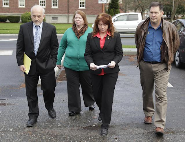 Kari Bales, second from left, walks with attorney Lance Rosen, left, her sister, Stephanie Tandberg, second from right, and Tandberg's husband Eric Tandberg, right, as they prepare to to talk to reporters Tuesday Nov. 13, 2012, outside the building housing a military courtroom on Joint Base Lewis McChord in Washington state, where a preliminary hearing ended Tuesday for Kari's husband, U.S. Army Staff Sgt. Robert Bales. Bales is accused of 16 counts of premeditated murder and six counts of attempted murder for a pre-dawn attack on two villages in Kandahar Province in Afghanistan last March. (AP Photo/Ted S. Warren)