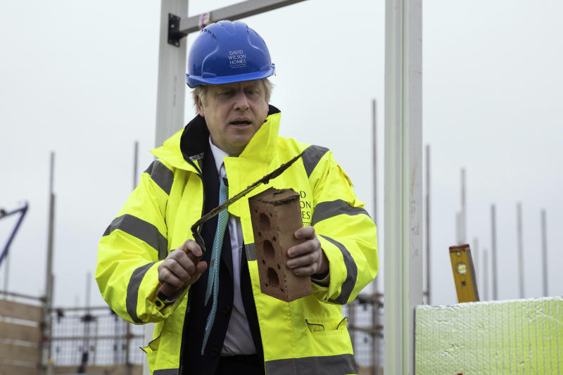 Britain's Prime Minister Boris Johnson lays a brick during a visit to the Barratt Homes - Willow Grove housing development in Bedford, England, Thursday, Nov. 21, 2019. Britain's main opposition Labour Party promised Thursday to radically expand public spending and state ownership if it wins the Dec. 12 election, trying to close an opinion-poll gap with the governing Conservatives (Dan Kitwood/Pool photo via AP)