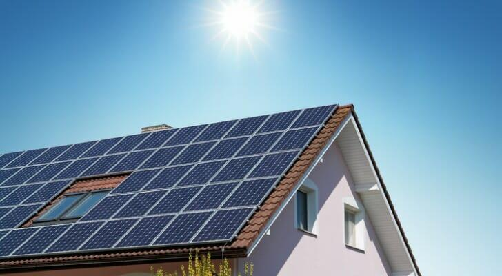 Image shows a home standing against a background of a bright blue sky with the sun shining directly overhead; the slanted roof of the home is covered in solar panels. SmartAsset conducted this study to investigate the financial value of residential solar panels.