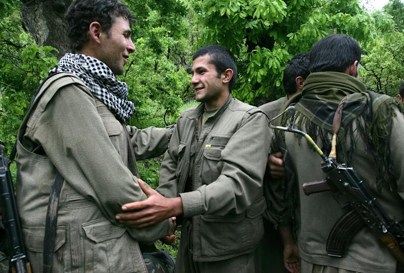 Kurdish fighters from the Kurdistan Workers Party (PKK) congratulate each other after arriving in the Heror area, northeast of Dahuk, 260 miles (430 kilometers) northwest of Baghdad, Iraq, Tuesday, May 14, 2013. The first of Kurdish fighters from Turkey have entered northern Iraq as part of a peace deal to end a long uprising, despite Iraqi objections to the transfer. Comrades greeted 13 armed men and women from the Kurdistan Workers Party (PKK) at a ceremony in Heror in Iraq's self-ruled Kurdish area. The central government in Baghdad has rejected the deal, warning that the entry of more armed Kurdish fighters could harm the country's security. (AP Photo/ Ceerwan Aziz)