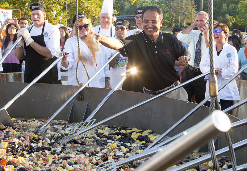 This Monday, Sept. 3, 2012 photo released by the University of Massachusetts in Amherst, Mass., shows Chancellor Kumble Subbaswamya adding ingredients to a seafood stew cooking at a Labor Day barbecue to celebrate the return of students to the campus. Chefs at the university set a new Guinness World Record by cooking the 6,656-pound seafood stew in the same custom-built, 1-ton, 14-foot frying pan used last year to set a Guinness Record of 4,010 pounds for the world's largest stir-fry. (AP Photo/University of Massachusetts Amherst, John Solem)