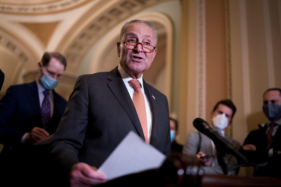Senate Majority Leader Chuck Schumer, D-N.Y., joined at left by Sen. Ron Wyden, D-Ore., chair of the Senate Finance Committee, speaks to reporters Tuesday after a weekly policy meeting, at the Capitol in Washington, D.C.