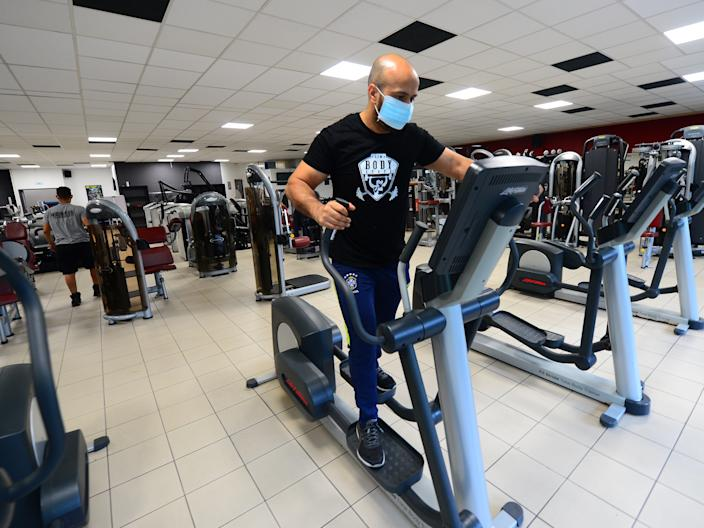 "Coach and manager of ""Body Staff Gym"" fitness centre Mabchour Mourad tests a machine on June 1, 2020, in Artigues-pres-Bordeaux, southwestern France, on the eve of the reopening of the gym"