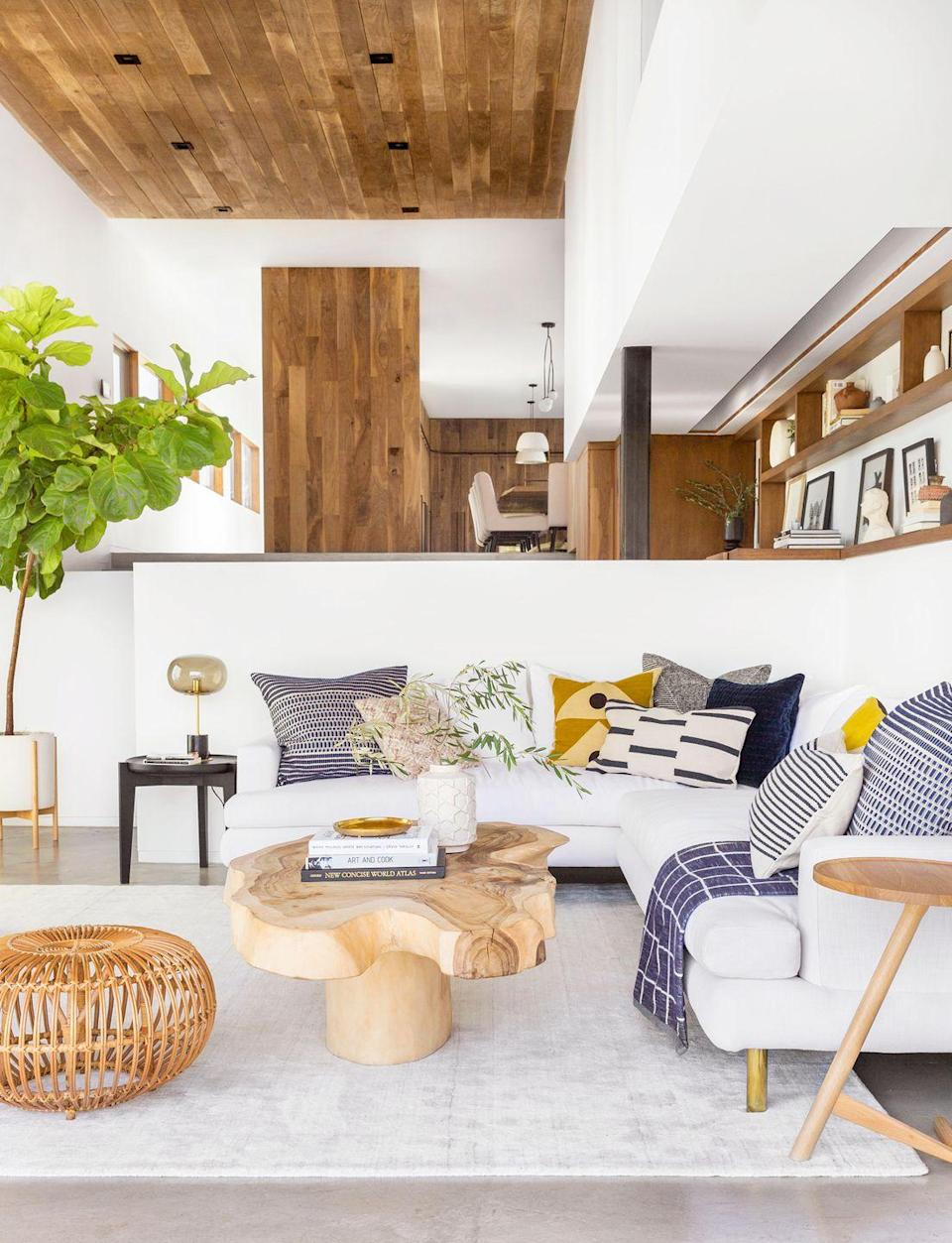 """<p><a href=""""https://stylebyemilyhenderson.com/"""" rel=""""nofollow noopener"""" target=""""_blank"""" data-ylk=""""slk:Emily Henderson"""" class=""""link rapid-noclick-resp"""">Emily Henderson</a> creates visual consistency in this spacious, open environment by bringing the wood walls in the dining room into the entryway and living room—but this time, on the ceiling. </p>"""