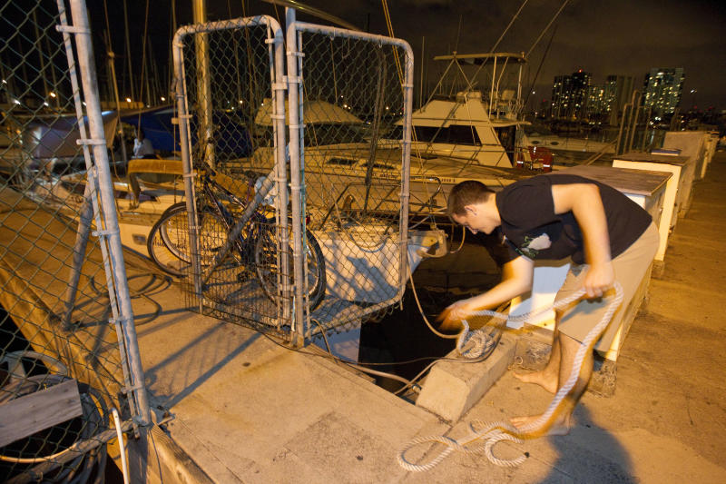 Tad Kanski of Newport Beach, Calif unties his family's sailboat moored at the Ala Wai Harbor after learning of a tsunami warning Saturday, Oct. 27, 2012, in Honolulu. A tsunami warning has been issued for Hawaii after a 7.7-magnitude earthquake rocked an island off the west coast of Canada. The Pacific Tsunami Warning Center originally said there was no threat to the islands, but a warning was issued later Saturday and remains in effect until 7 p.m. Sunday. A small craft advisory is in effect until Sunday morning.(AP Photo/Eugene Tanner)