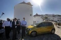 Greek Prime Minister Kyriakos Mitsotakis, right, listens Volkswagen Group CEO Herbert Diess, center, during the official launch of a project to introduce and test electric vehicles and sustainable energy systems on the Aegean Sea island of Astypalea, Greece, on Wednesday, June 2, 2021. The government has partnered with the German carmaker on the island project aimed a switching to electric vehicle use over the next five years. (Alexandros Vlachos/Pool via AP)