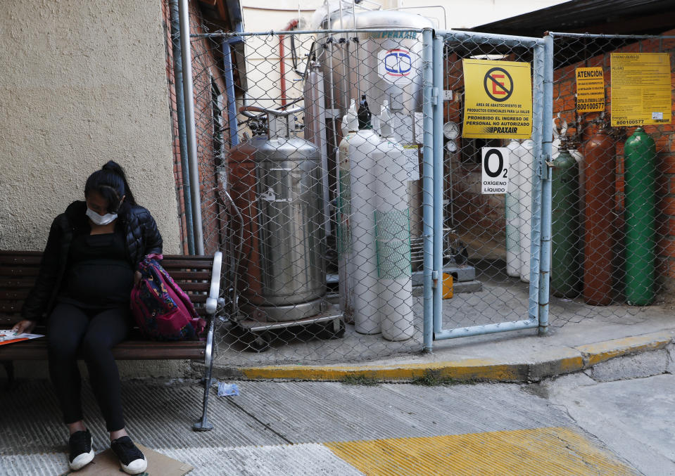 A pregnant woman waiting to be attended sits on a bench situated next to an oxygen tank storage area, outside the Women's Hospital, in La Paz, Bolivia, Thursday, Aug. 13, 2020. Doctors say the supply of oxygen for babies in the intensive care unit is becoming scarce, the result of nationwide blockades by supporters of the party of former President Evo Morales who object to the recent postponement of elections. Bolivia's political and social crisis is coinciding with the continued spread of the new coronavirus. (AP Photo/Juan Karita)
