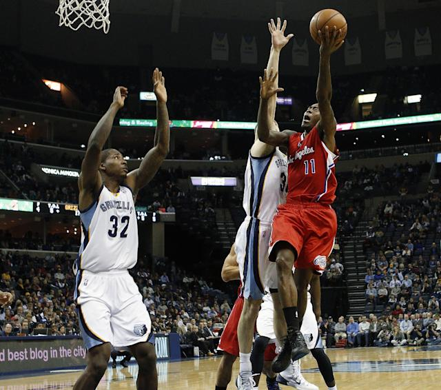 Los Angeles Clippers guard Jamal Crawford (11) goes to the basket against Memphis Grizzlies forward Ed Davis (32) and Jon Leuer, back, in the first half of an NBA basketball game on Thursday, Dec. 5, 2013, in Memphis, Tenn. (AP Photo/Lance Murphey)