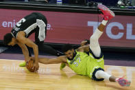Minnesota Timberwolves' Karl-Anthony Towns , right, sprawls on the court and tries to get the ball away from San Antonio Spurs' Keldon Johnson in the second half of an NBA basketball game Saturday, Jan. 9, 2021, in Minneapolis. (AP Photo/Jim Mone)