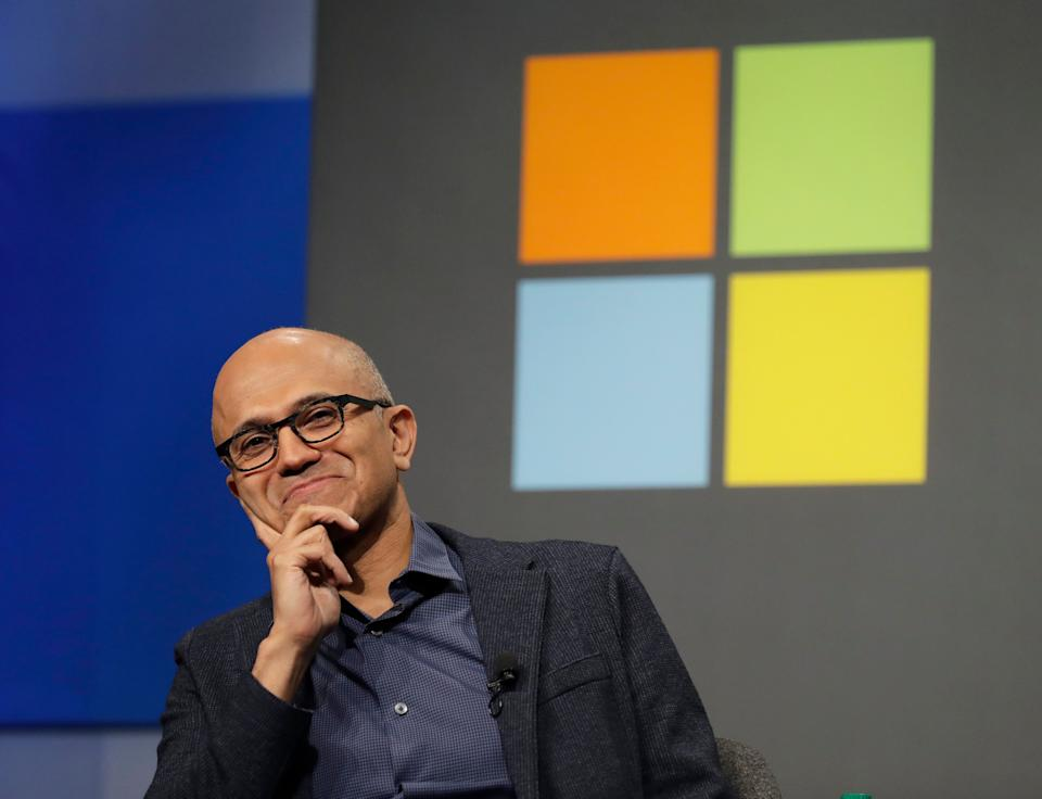 FILE- In this Wednesday, Nov. 28, 2018, file photo Microsoft CEO Satya Nadella listens to a question as he sits in front of the Windows logo during the annual Microsoft Corp. shareholders meeting in Bellevue, Wash. Microsoft, the 1990s home-computing powerhouse that is having a renaissance moment, has eclipsed Amazon and is close to passing Apple in market value. Around midday Thursday, Apple's value topped Microsoft's by just over $2 billion, $847.6 billion to $845.2 billion. Amazon was back to $820.8 billion. That Microsoft is even close to eclipsing Apple would have been unheard of just a few years ago. (AP Photo/Ted S. Warren, File)