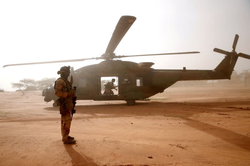 FILE PHOTO: FILE PHOTO: A French soldier stands guards in front of an NH90 Caiman military helicopter during Operation Barkhane in Ndaki
