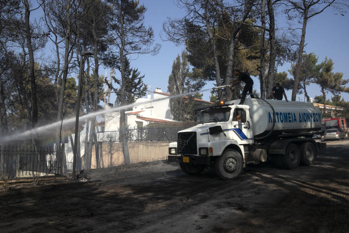 Municipal workers spray water during a forest fire at Dionysos northern suburb of Athens, on Tuesday, July 27, 2021. Greek authorities have evacuated several areas north of Athens as a wildfire swept through a hillside forest and threatened homes despite a large operation mounted by firefighters. (AP Photo/Yorgos Karahalis)