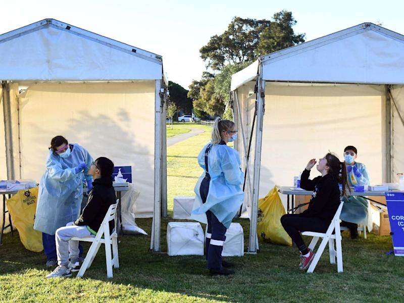 People have swab samples taken during testing for the COVID-19 coronavirus in a suburban park in Melbourne: AFP via Getty Images