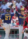 Milwaukee Brewers' Willy Adames (27) celebrates with Christian Yelich after hitting a home run during the ninth inning of the team's baseball game against the Cincinnati Reds in Cincinnati, Sunday, July 18, 2021. (AP Photo/Bryan Woolston)