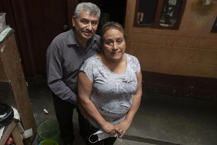 """Fabio Rodolfo Vasquez and his wife, Maria Moreno, pose for photo in the home of Moreno's mother, in the San Pedrito neighborhood of Guatemala City, Thursday, Sept. 17, 2020. A homemade video where they dance to """"Danger"""" by The Flirts went viral, and the couple, who met on the dance floor more than 30 years ago, became an overnight sensation. (AP Photo/Moises Castillo)"""