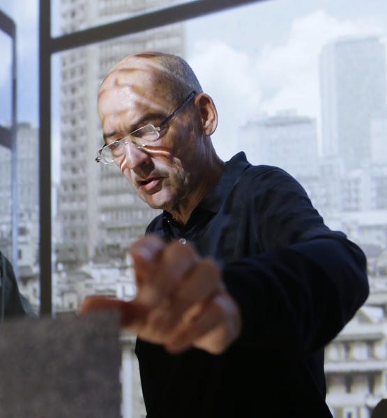 "Dutch architect Rem Koolhose gestures at the Knoll industrial design house's space, part of the Milan's Furniture Fair, in Milan, Italy, Monday, April 8, 2013. Rem Koolhaas says he has shed his ""puritanical"" attitude against architects designing objects, and has shifted scale to create 11 pieces of furniture for U.S. industrial design house Knoll. The Dutch architect's creations, premiered Monday ahead of Milan Design Week, include a dynamic counter a stack of three horizontal beams that can be transformed from a screen-like unit to cantilevered shelves and benches that invite people to sit, climb and lean in a sort of social/intellectual romper room. The Koolhaas collection, celebrating Knoll's 75th anniversary, previewed at the Prada showroom linking architecture, design and fashion. (AP Photo/Luca Bruno)"