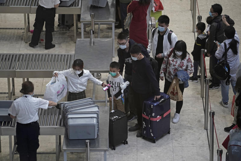 Passengers cross the security check at the departure hall of the high speed train station in Hong Kong, Thursday, Jan. 23, 2020. China closed off a city of more than 11 million people Thursday, halting transportation and warning against public gatherings, to try to stop the spread of a deadly new virus that has sickened hundreds and spread to other cities and countries in the Lunar New Year travel rush. (AP Photo/Kin Cheung)