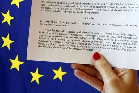 FILE PHOTO - Article 50 of the EU's Lisbon Treaty is pictured near an EU flag following Britain's referendum results to leave the European Union, in this photo illustration taken in Brussels