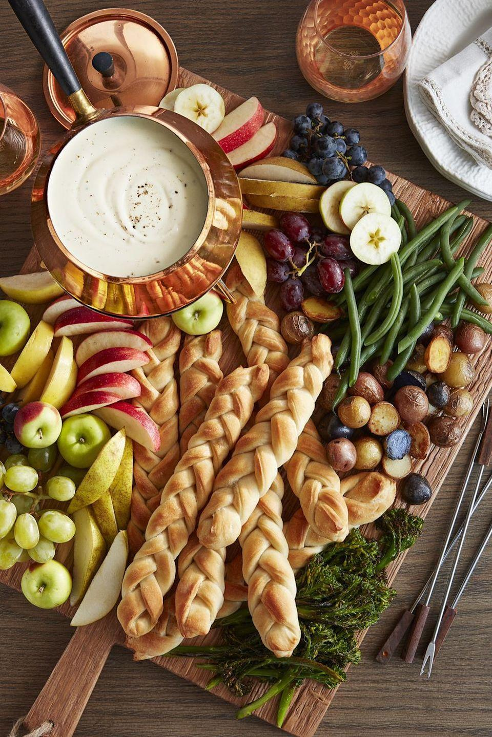 """<p>It doesn't get much easier than these braided breadsticks. You can use either store-bought or homemade pizza dough in this recipe—but your guests won't know the difference. They'll be too busy enjoying the decadent <a href=""""https://www.countryliving.com/food-drinks/a28068814/three-cheese-fondue-recipe/"""" rel=""""nofollow noopener"""" target=""""_blank"""" data-ylk=""""slk:three-cheese fondue"""" class=""""link rapid-noclick-resp"""">three-cheese fondue</a>. </p><p><strong><a href=""""https://www.countryliving.com/food-drinks/a28069249/cable-knit-breadsticks-recipe/"""" rel=""""nofollow noopener"""" target=""""_blank"""" data-ylk=""""slk:Get the recipe"""" class=""""link rapid-noclick-resp"""">Get the recipe</a>.</strong> </p>"""