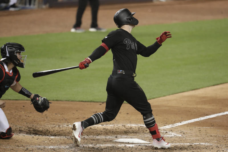 Philadelphia Phillies' Corey Dickerson, right, follows through on a three-run double during the seventh inning of a baseball game against the Miami Marlins, Saturday, Aug. 24, 2019, in Miami. (AP Photo/Lynne Sladky)