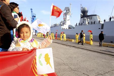 A child waves national flags of China (top) and Cyprus as the Chinese frigate Yancheng (R) comes in to dock at Limassol port, January 4, 2014. REUTERS/Andreas Manolis