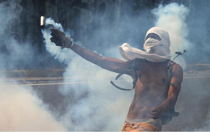 A demonstrator returns a canister of tear gas towards security forces during anti-government protests in Caracas, Venezuela - Credit: AP