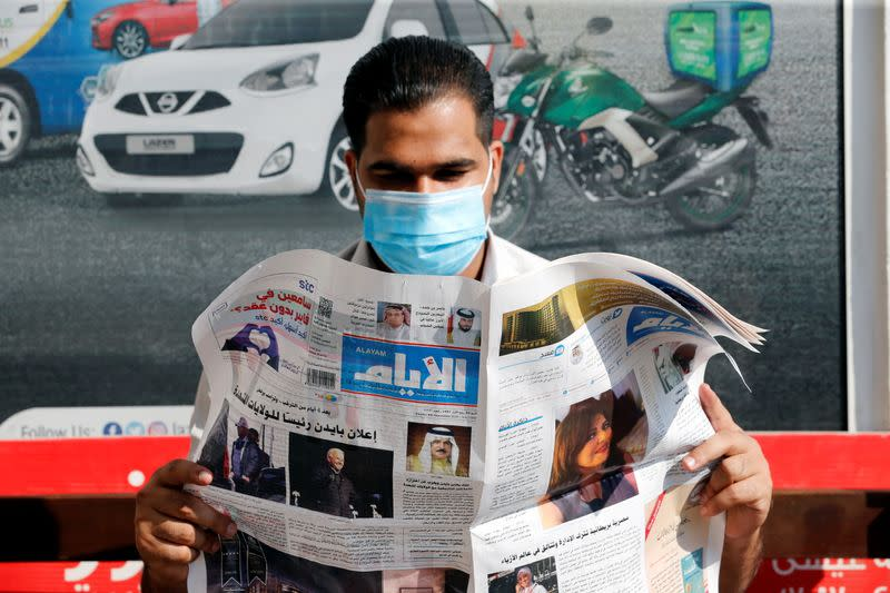 A man wears a face mask as he reads a newspaper with the front page headline reporting on Joe Biden's U.S. presidential election victory, in Manama