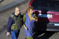 "A Georgian police officer escorts a woman who escaped from a bank where an armed assailant has taken several people hostage, in the town of Zugdidi in western Georgia, Wednesday, Oct. 21, 2020. An armed assailant took several people hostage at a bank in the ex-Soviet nation of Georgia on Wednesday, authorities said. The Georgian Interior Ministry didn't immediately say how many people have been taken hostage in the town of Zugdidi in western Georgia, or what demands the assailant has made. Police sealed off the area and launched an operation ""to neutralize the assailant,"" the ministry said in a statement. (AP Photo/Zurab Tsertsvadze)"