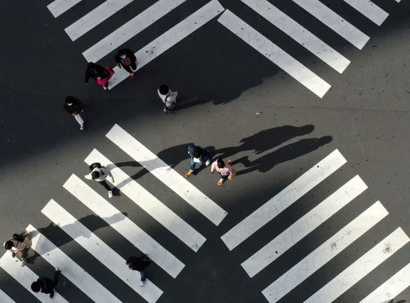 FILE PHOTO: People cross a street in front of Shinjuku station in Tokyo