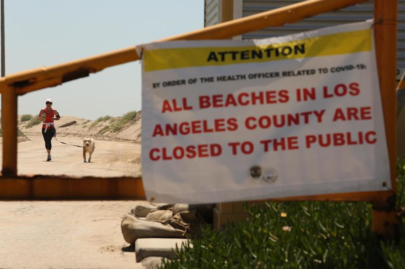 A jogger and her dog run on a closed road at Westward Beach in Malibu. The beach has been temporarily closed in an effort to help stop the spread of the coronavirus.
