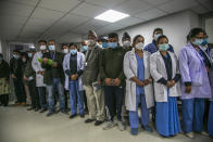 Nepalese health workers observe a minute of silence in memory of people who died due to COVID-19 before administering vaccine at Teaching Hospital in Kathmandu, Nepal, Wednesday, Jan. 27, 2021. Thousands of health workers lined up across Nepal to get the coronavirus vaccine Wednesday as the Himalayan nation began its campaign to get the population vaccinated within three months. Neighboring India gifted Nepal 1 million doses of the AstraZeneca-Oxford University vaccine manufactured under license by the Serum Institute of India. (AP Photo/Niranjan Shrestha)