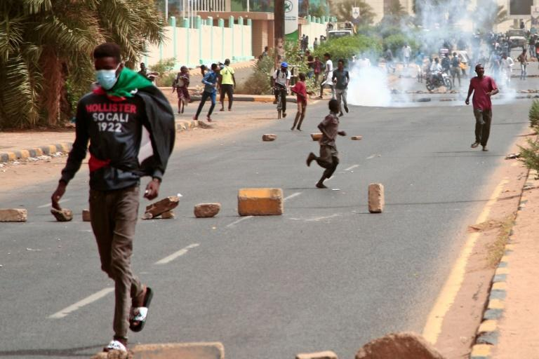 Sudanese protesters run from tear gas fired by security forces during a demonstration in Omdurman, Khartoum's twin city, on June 30, 2021 after IMF-backed reforms to slash fuel subsidies (AFP/Ebrahim HAMID)
