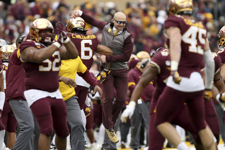 Minnesota head coach P.J. Fleck, center, jumps in celebration with defensive back Chris Williamson after a defense stop against Penn State. (AP)