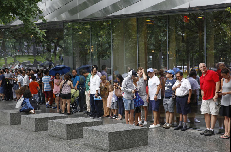 "In this July 11, 2017 photo, visitors to the National September 11 Memorial and Museum take shelter beneath a museum overhang during a sudden rainstorm in New York. Last winter the U.S. tourism industry worried about a ""Trump slump,"" fearing that Trump administration policies might discourage international travelers from visiting the U.S. But statistics from the first half of 2017 suggest that the travel to the U.S. is robust and a number of sectors have reported increased international visitation, with one expert calling it a ""Trump bump."" The museum is among those reporting more international visitors this year compared to the same period in 2016. (AP Photo/Kathy Willens)"