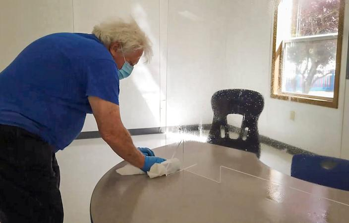 A Lakewood Public Schools custodian cleans up a desk set up with a plexiglass shield for in-person evaluations for incoming students with special needs. Incoming public schools students from any age are being tested on their learning and speech skills; evaluated for occupational and physical therapies; evaluated psychologically; and assessed for their English Language Learner level.
