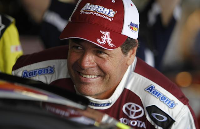 File-This May 3, 2013 file photo shows driver Michael Waltrip talking with other drivers during practice for Sunday's NASCAR Sprint Cup series auto race at Talladega Superspeedway in Talladega, Ala. The Associated Press has learned that Michael Waltrip Racing will run only two full-time cars next season because of the loss of sponsor NAPA. Team owners Michael Waltrip and Rob Kauffman on Monday Oct. 14, 2013, began telling employees of their decision. Those affected were told they are free to begin looking for a new job immediately. (AP Photo/Butch Dill, File)