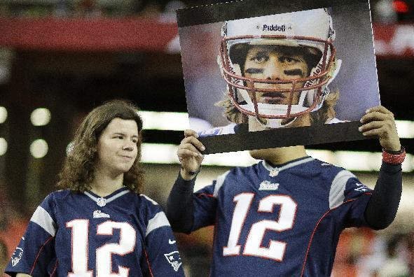 Mike Gallegos, holding a Patriots quarterback Tom Brady photo and Alyssa Gautrau, of Fort Benning Ga., watch players work out before the first half of an NFL football game against the Atlanta Falcons, Sunday, Sept. 29, 2013, in Atlanta. (AP Photo/David Goldman)
