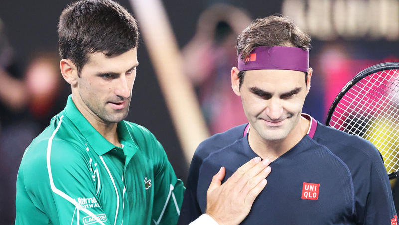 Serbia's Novak Djokovic (L) pats Switzerland's Roger Federer after his victory during their men's singles semi-final match on day eleven of the Australian Open tennis tournament in Melbourne on January 30, 2020. (Photo by DAVID GRAY / AFP)