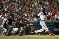 Atlanta Braves' Nick Markakis hits a sacrifice fly ball in front of Washington Nationals catcher Yan Gomes and umpire Rob Drake in the fifth inning of a baseball game against the Washington Nationals, Friday, Sept. 13, 2019, in Washington. Ronald Acua Jr. scored on the play. (AP Photo/Patrick Semansky)