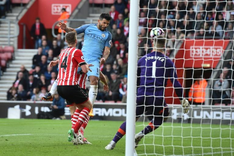 Manchester City's Sergio Aguero jumps to head their third goal past Southampton's goalkeeper Fraser Forster (R) during their match at St Mary's Stadium in Southampton, southern England on April 15, 2017