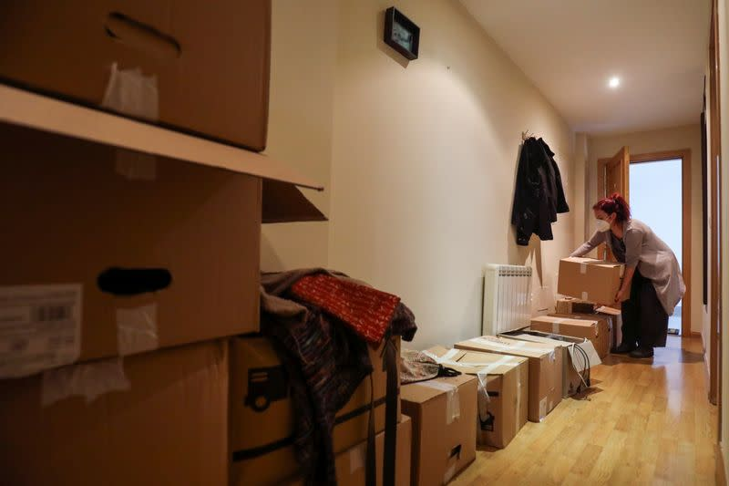 Ines Alcolea places moving boxes in her new rented apartment in Fuensalida